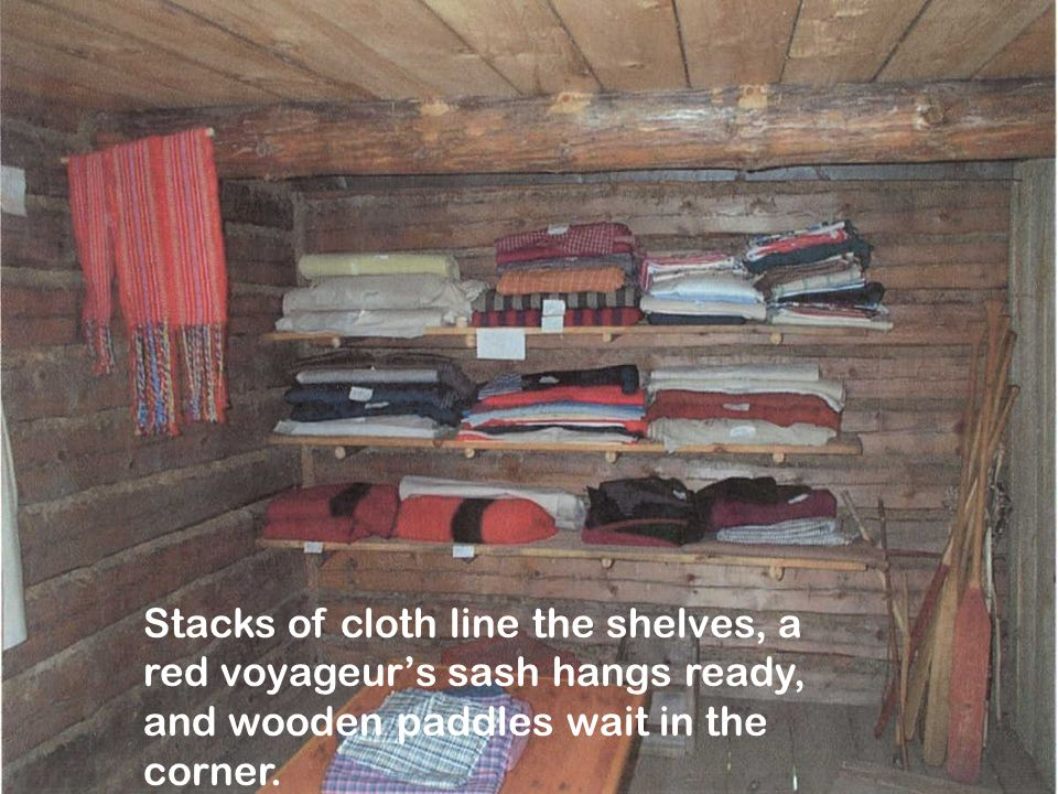 Stacks of cloth line the shelves, a red voyageurs sash hangs ready, and wooden paddles wait in the corner.