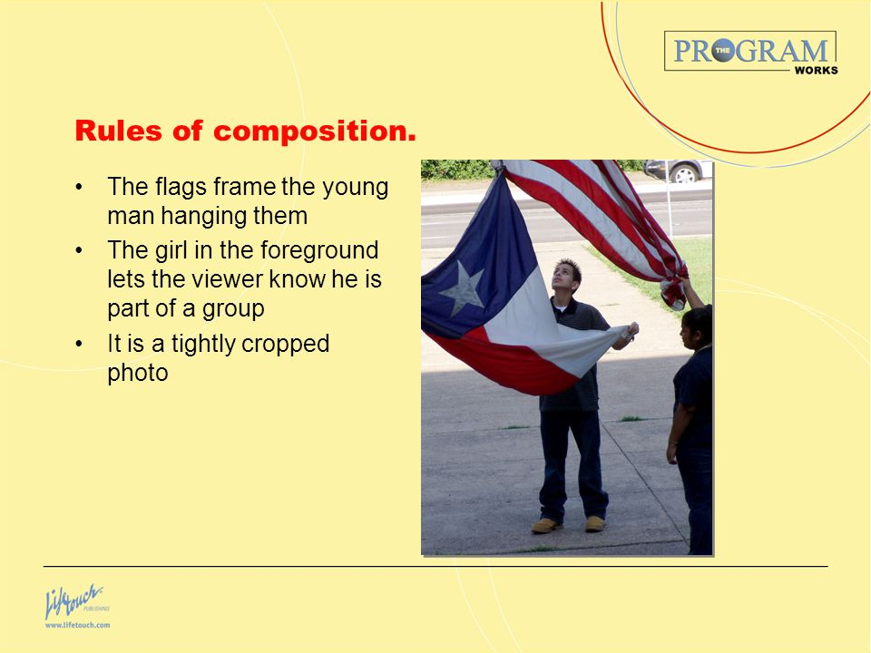 Rules of composition. The flags frame the young man hanging them The girl in the foreground lets the viewer know he is part of a group It is a tightly