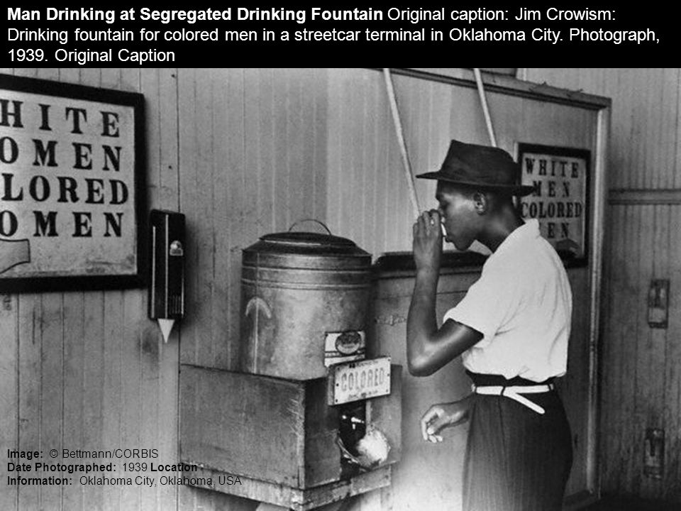 Man Drinking at Segregated Drinking Fountain Original caption: Jim Crowism: Drinking fountain for colored men in a streetcar terminal in Oklahoma City