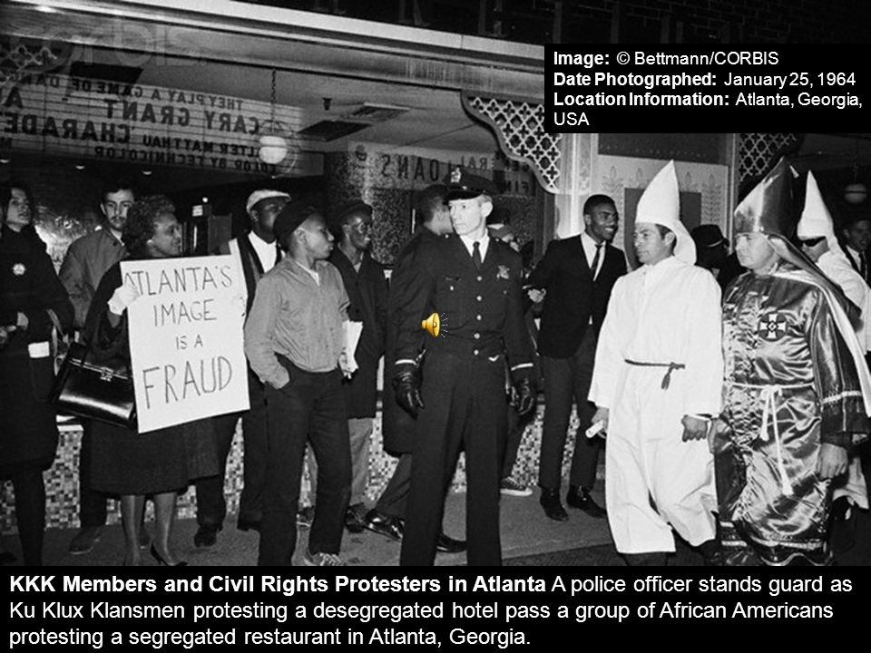 KKK Members and Civil Rights Protesters in Atlanta A police officer stands guard as Ku Klux Klansmen protesting a desegregated hotel pass a group of A