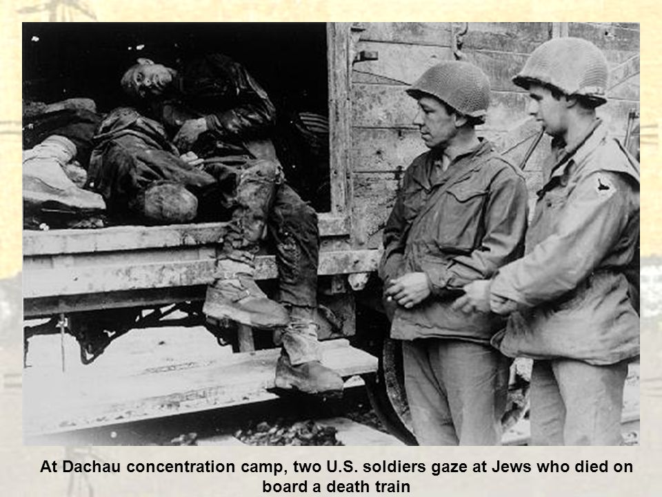At Dachau concentration camp, two U.S. soldiers gaze at Jews who died on board a death train
