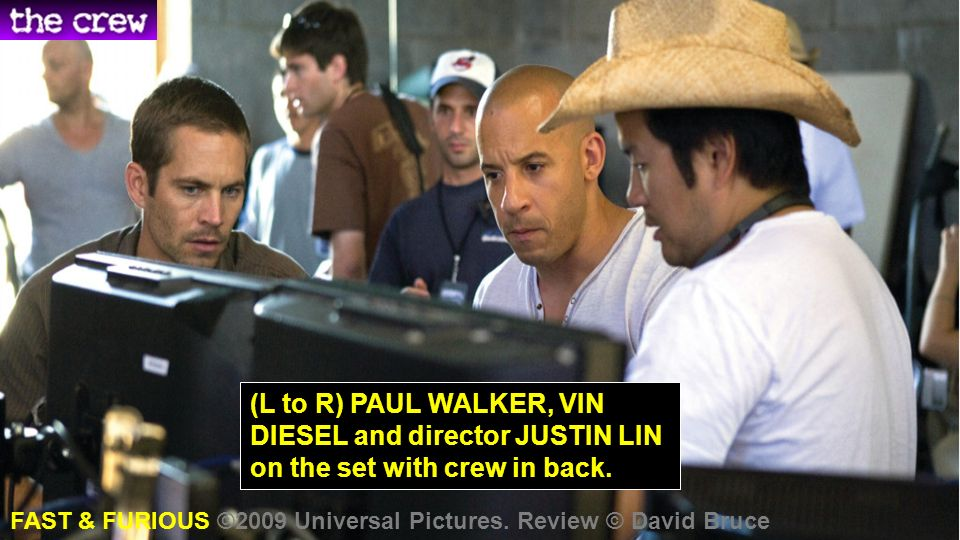 (L to R) PAUL WALKER, VIN DIESEL and director JUSTIN LIN on the set with crew in back.