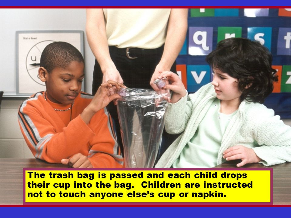 After wiping their mouth with the napkin, the children are instructed to gently push the napkin into the cup to absorb the liquid.