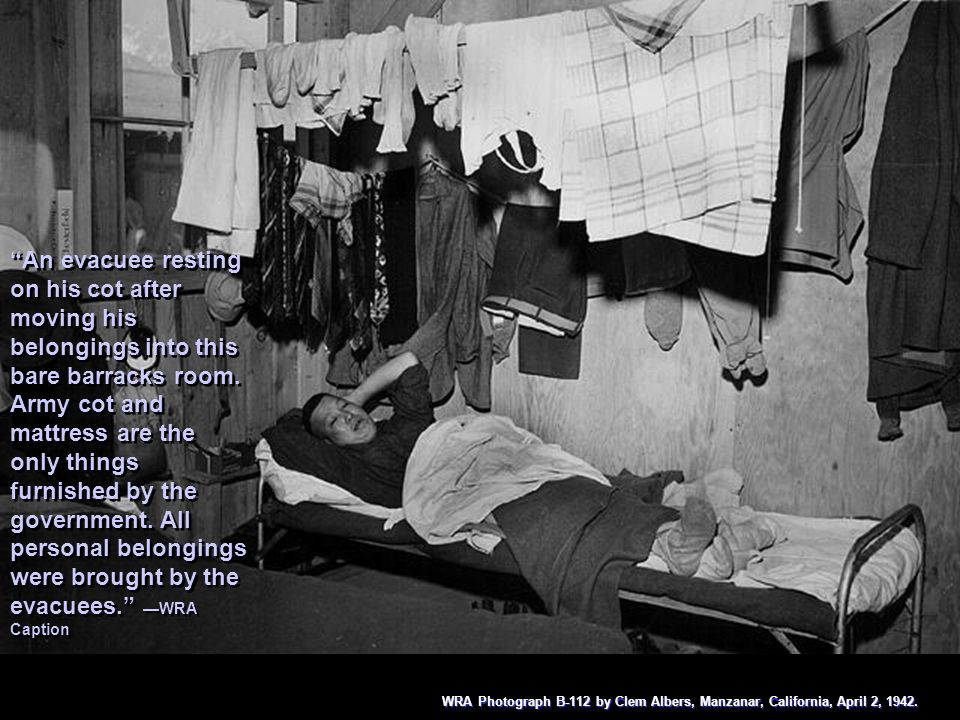 An evacuee resting on his cot after moving his belongings into this bare barracks room. Army cot and mattress are the only things furnished by the gov