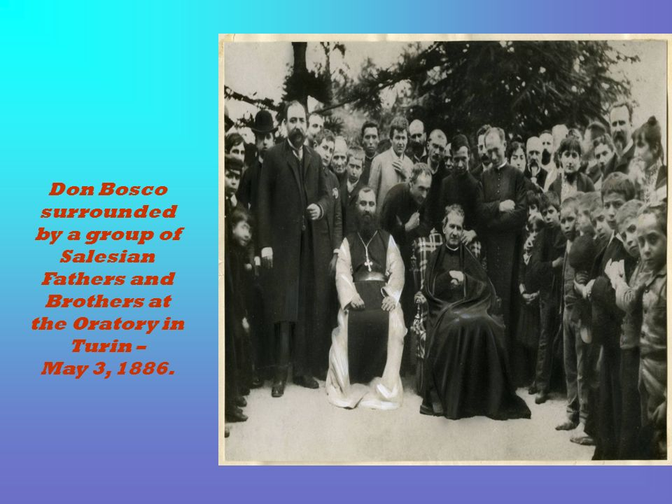Don Bosco surrounded by a group of Salesian Fathers and Brothers at the Oratory in Turin – May 3, 1886.