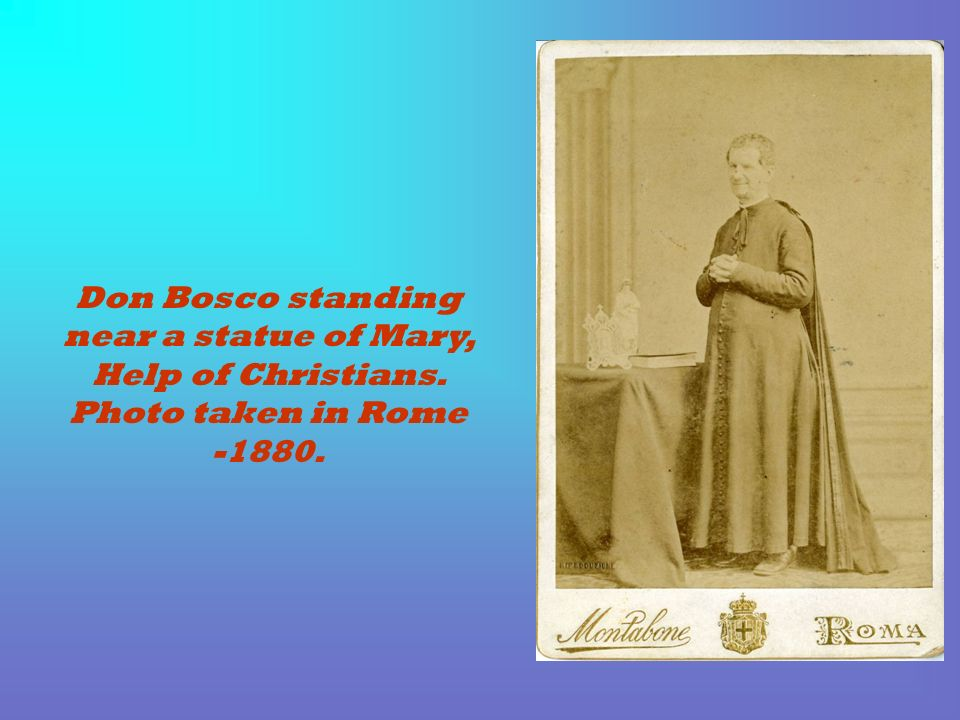 Don Bosco standing near a statue of Mary, Help of Christians. Photo taken in Rome -1880.
