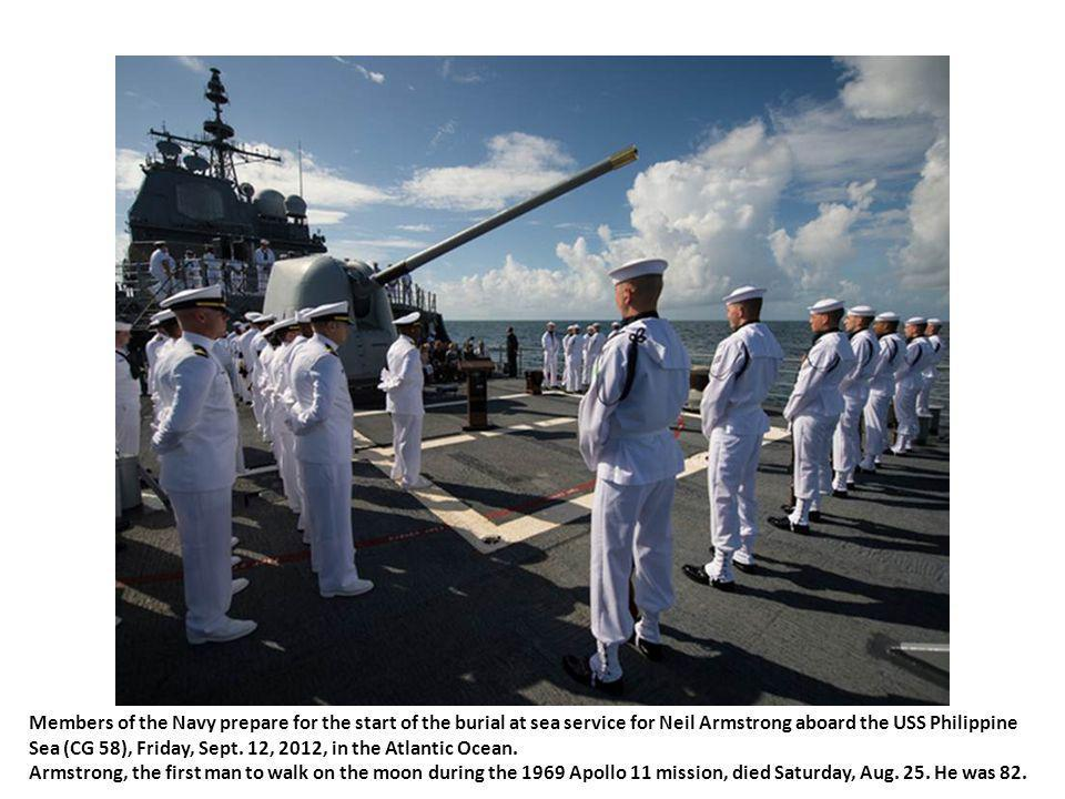 Members of the US Navy ceremonial guard hold an American flag over the cremains of Neil Armstrong, Apollo 11 commander and the first person to walk on the moon, during a burial at sea service aboard the USS Philippine Sea (CG 58), Friday, Sept.
