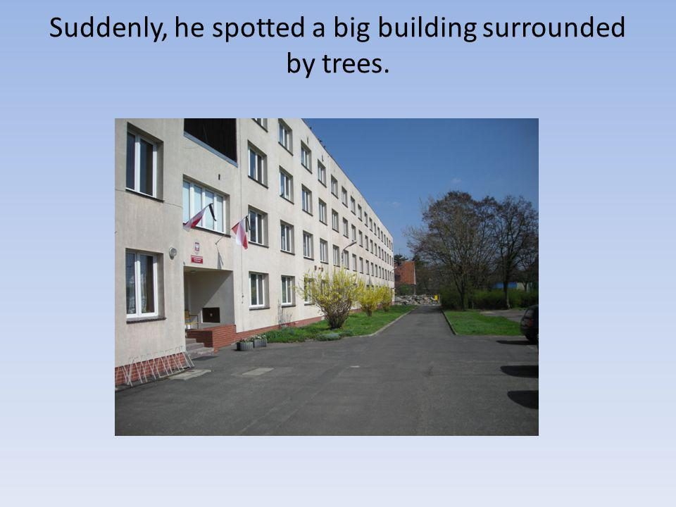 Suddenly, he spotted a big building surrounded by trees.