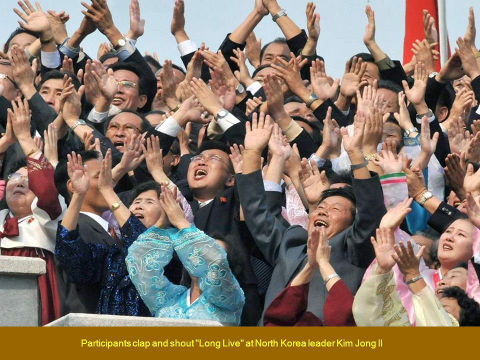 People in the audience applaud North Korean leader Kim Jong Il