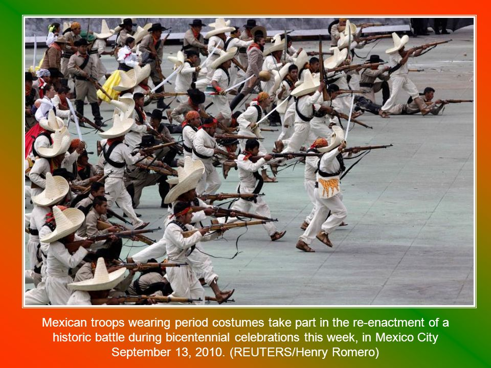 People watch members of the military perform reenactments of Mexico s historic battles during bicentennial celebrations in Mexico City, Monday Sept.