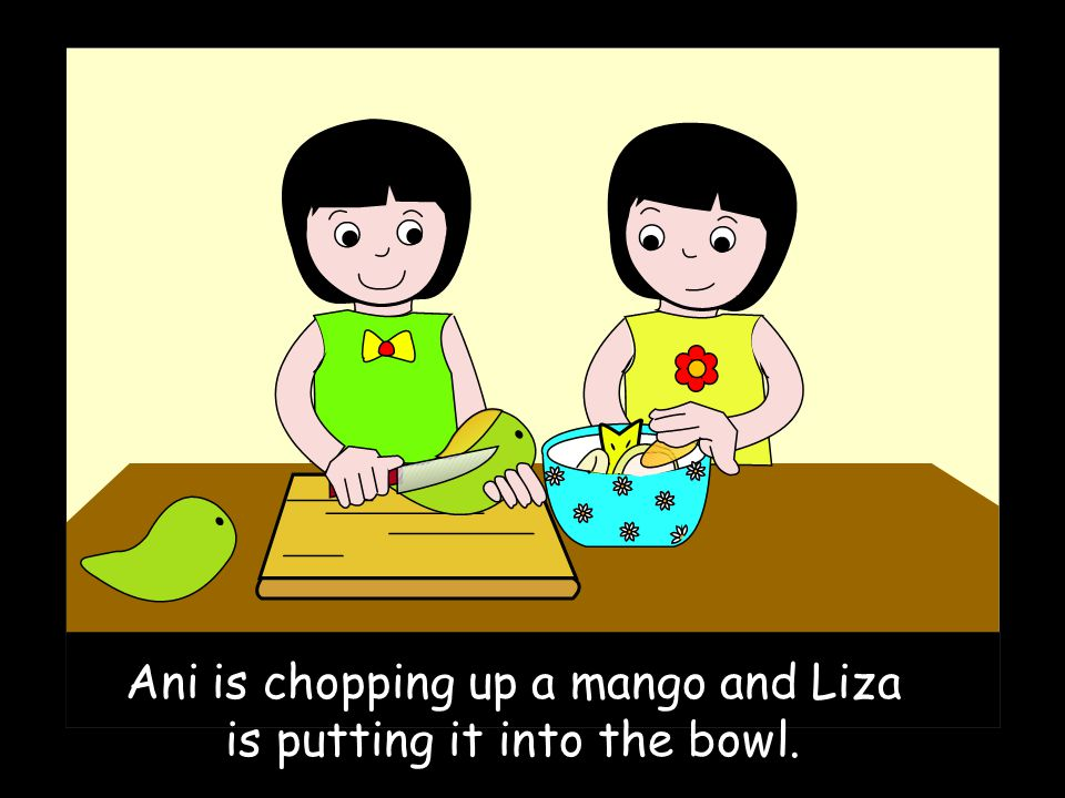 Ani is chopping up a mango and Liza is putting it into the bowl.