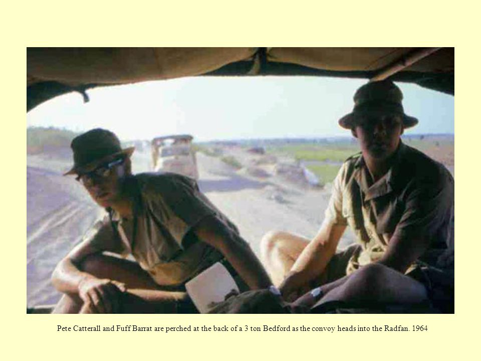 Pete Catterall and Fuff Barrat are perched at the back of a 3 ton Bedford as the convoy heads into the Radfan. 1964