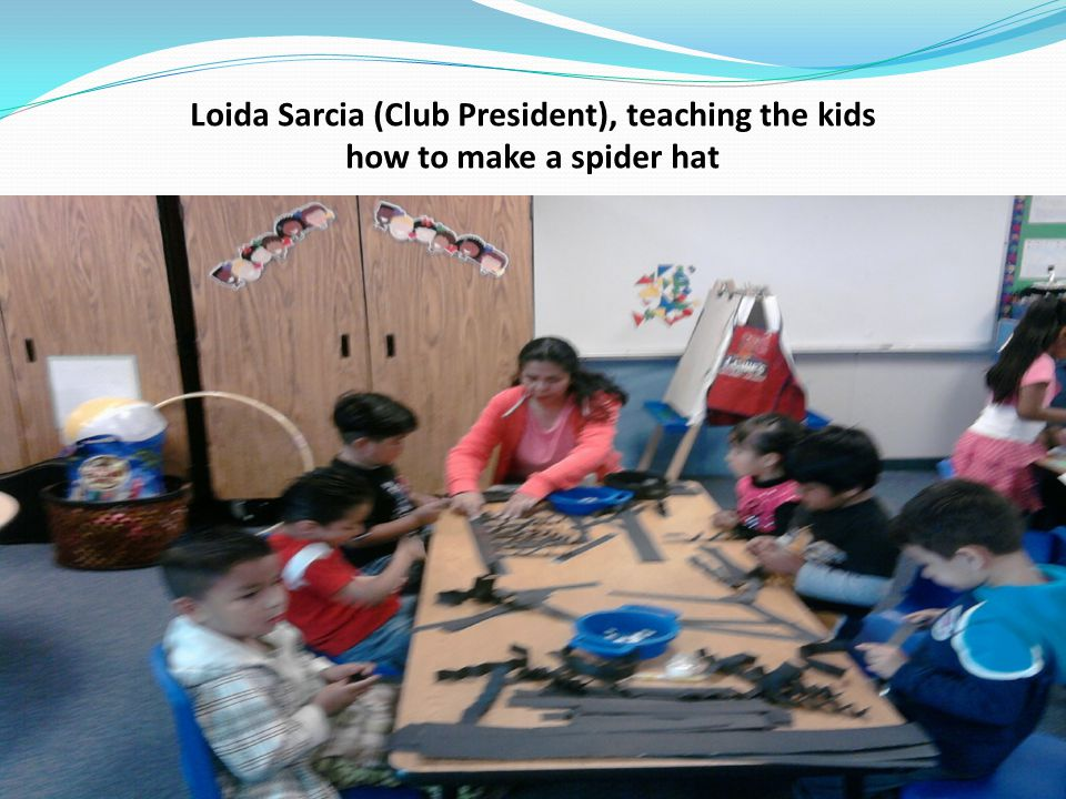 Loida Sarcia (Club President), teaching the kids how to make a spider hat