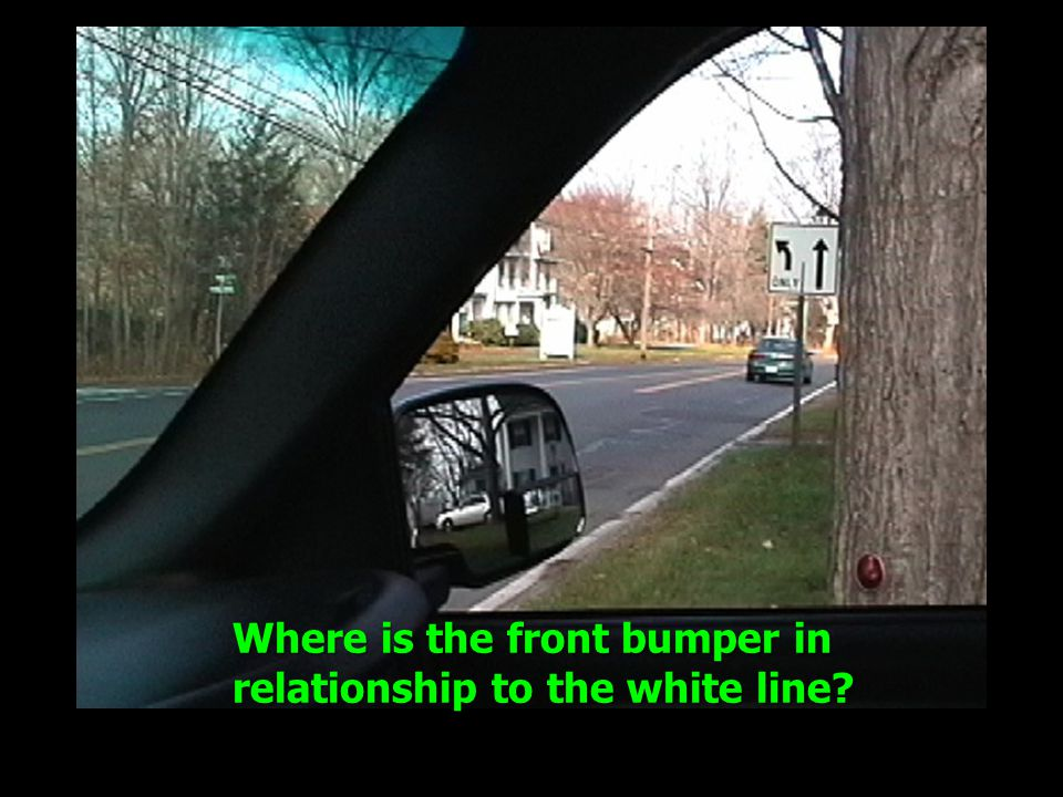 Where is the front bumper in relationship to the white line?