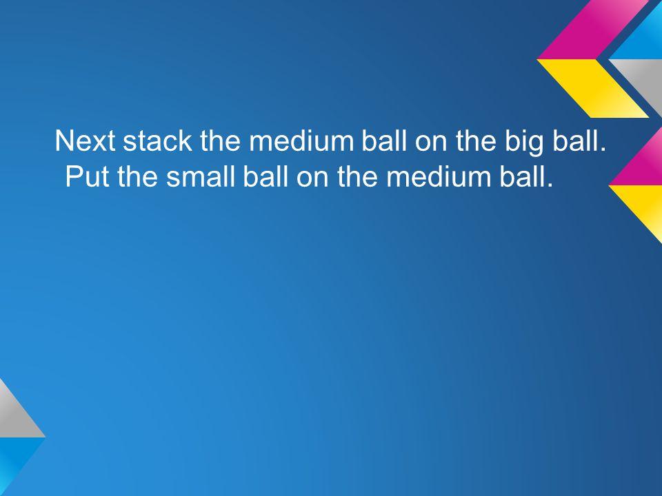 Next stack the medium ball on the big ball. Put the small ball on the medium ball.
