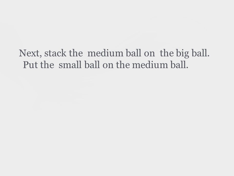 Next, stack the medium ball on the big ball. Put the small ball on the medium ball.