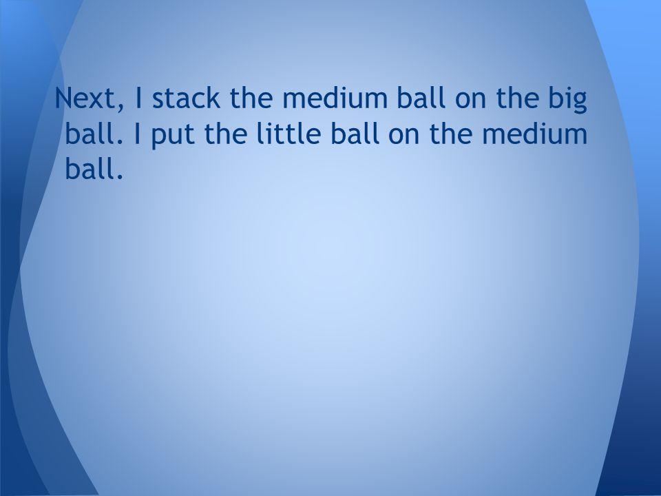 Next, I stack the medium ball on the big ball. I put the little ball on the medium ball.