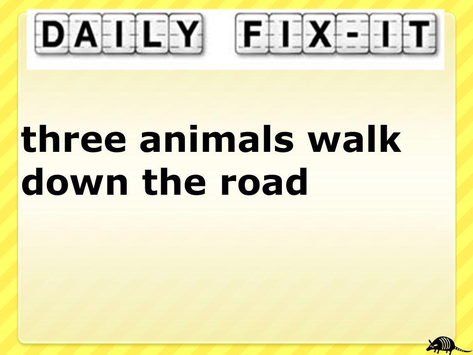 three animals walk down the road