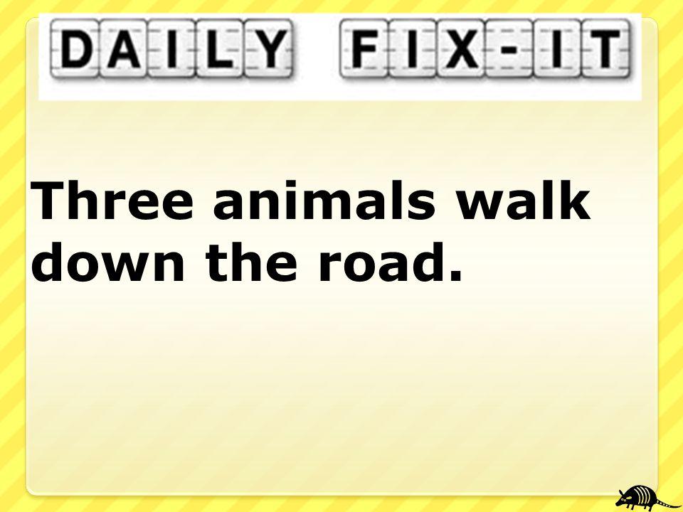Three animals walk down the road.