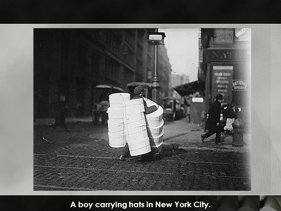 A boy carrying hats in New York City.
