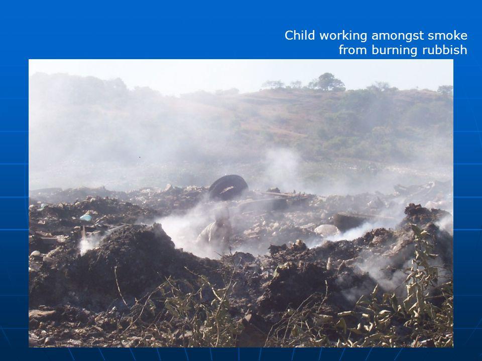 Child working amongst smoke from burning rubbish