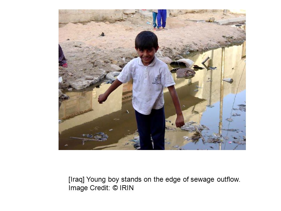 [Iraq] Young boy stands on the edge of sewage outflow. Image Credit: © IRIN