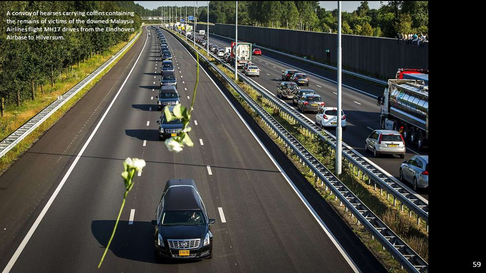 A convoy of hearses containing the remains of 40 victims of the Malaysia Airlines MH17 disaster drives past international flags as it leaves Eindhoven