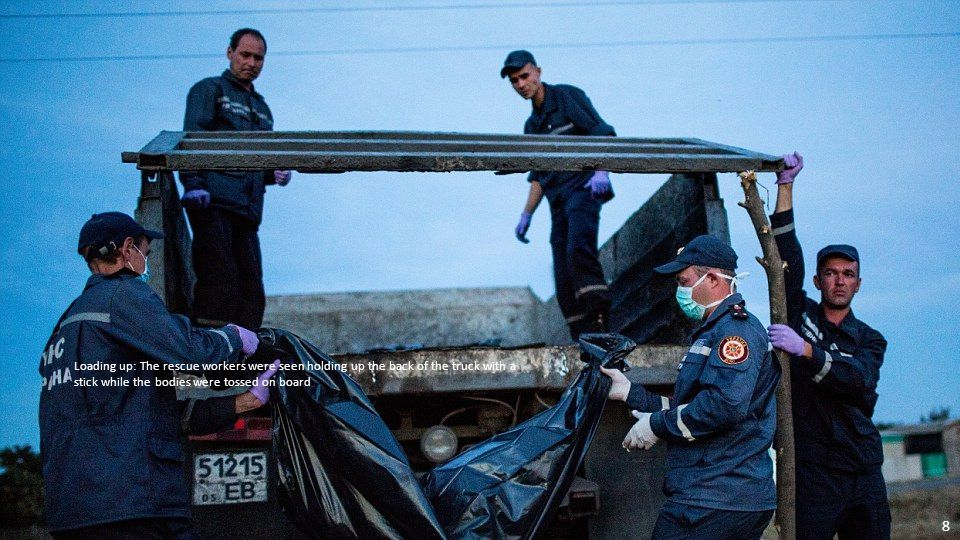 Piled up: Rescue workers are pictured above at the MH17 crash site in Grabovo, eastern Ukraine, moving bodies onto trucks 7
