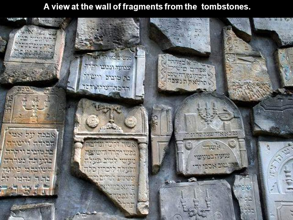 In front of the whole wall few monuments, through the fracture we can look inside, where the original cemetery drowned into the dark wood.