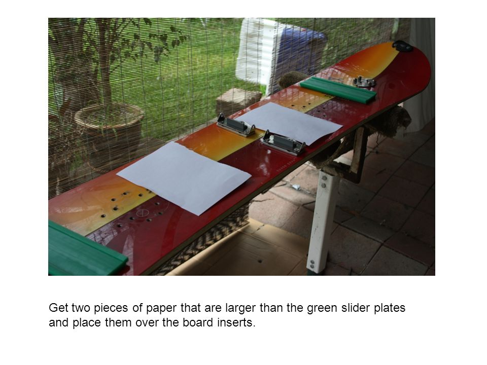 Get two pieces of paper that are larger than the green slider plates and place them over the board inserts.