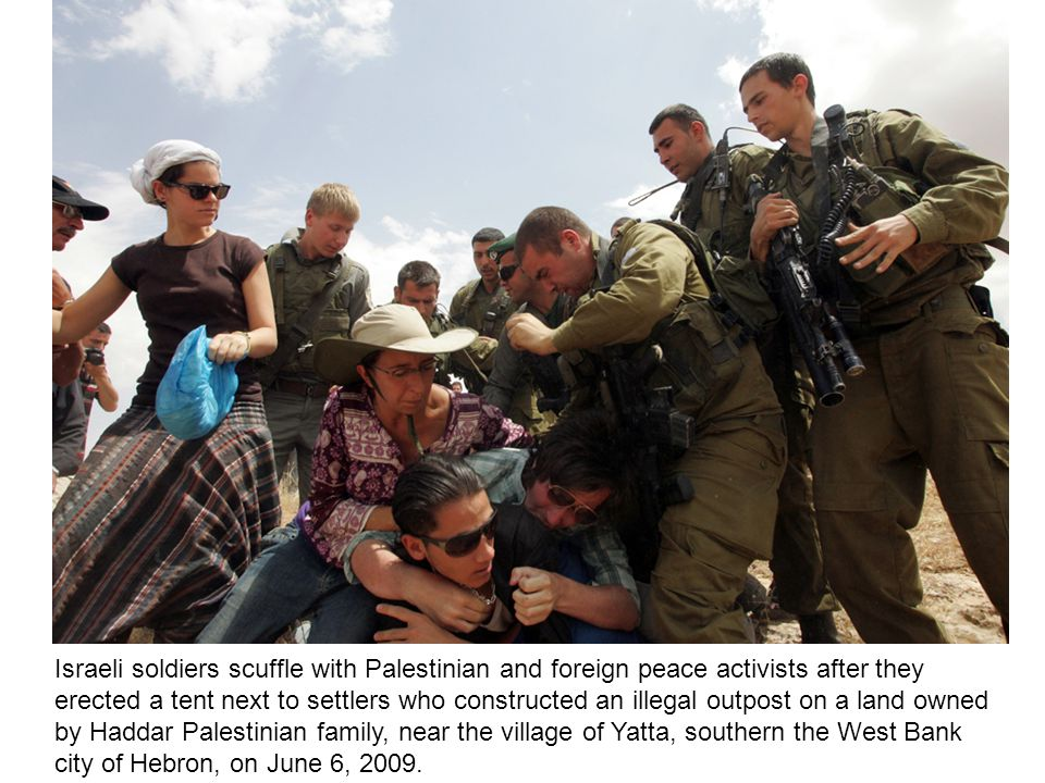 Israeli soldiers scuffle with Palestinian and foreign peace activists after they erected a tent next to settlers who constructed an illegal outpost on a land owned by Haddar Palestinian family, near the village of Yatta, southern the West Bank city of Hebron, on June 6, 2009.