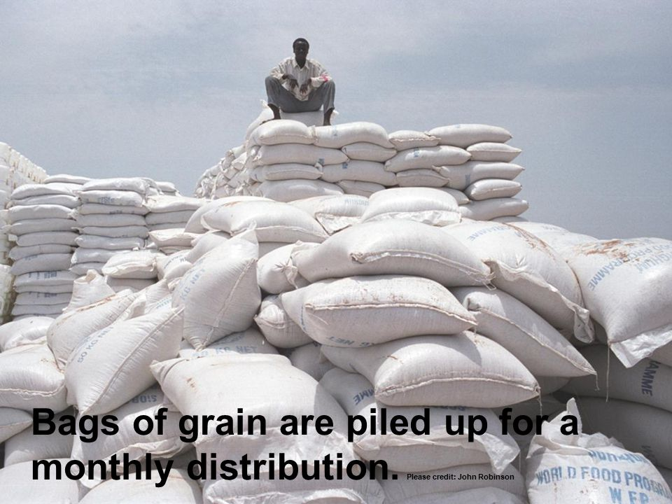 Bags of grain are piled up for a monthly distribution. Please credit: John Robinson