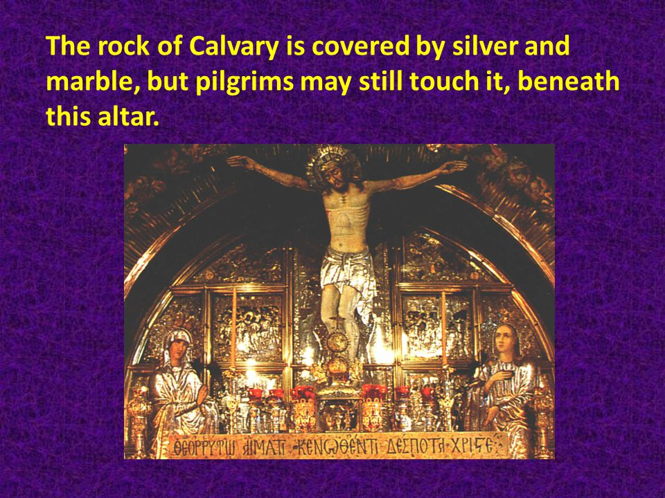 The rock of Calvary is covered by silver and marble, but pilgrims may still touch it, beneath this altar.