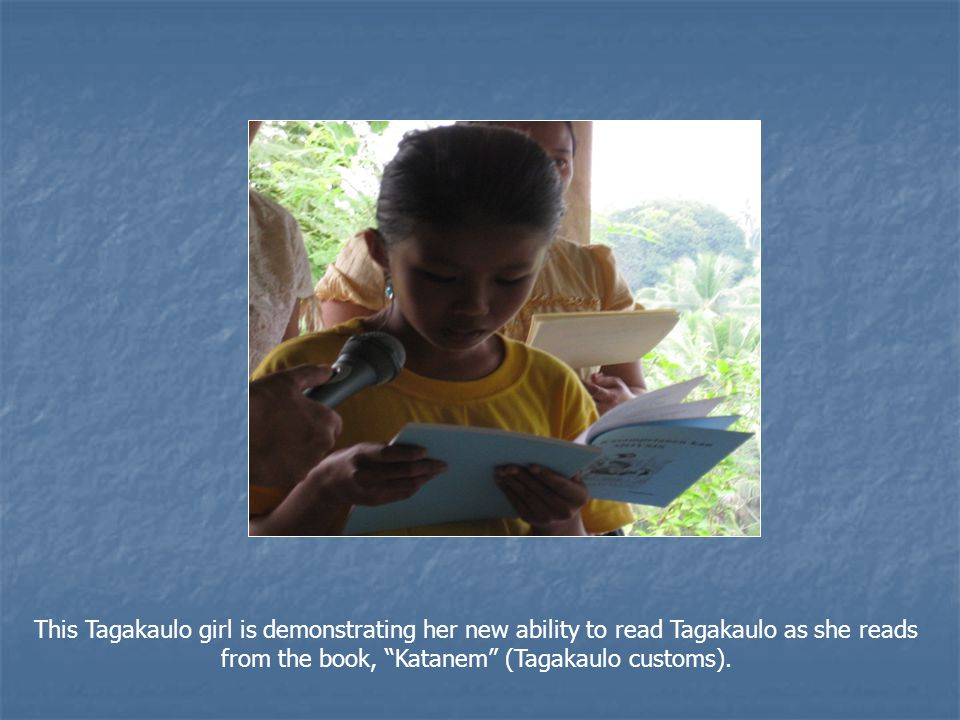 "This Tagakaulo girl is demonstrating her new ability to read Tagakaulo as she reads from the book, ""Katanem"" (Tagakaulo customs)."