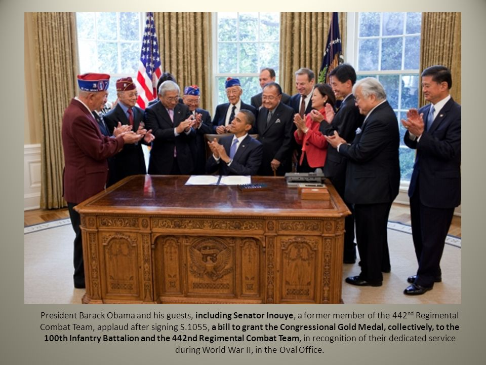President Barack Obama and his guests, including Senator Inouye, a former member of the 442 nd Regimental Combat Team, applaud after signing S.1055, a
