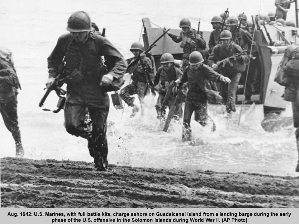16 Aug. 1942: U.S. Marines, with full battle kits, charge ashore on Guadalcanal Island from a landing barge during the early phase of the U.S. offensi