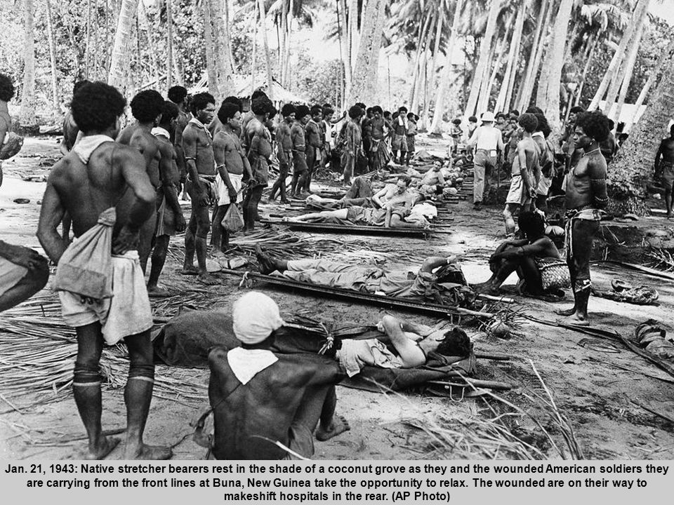 29 Jan. 21, 1943: Native stretcher bearers rest in the shade of a coconut grove as they and the wounded American soldiers they are carrying from the f