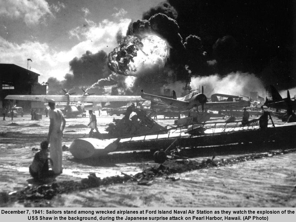 3 December 7, 1941: Sailors stand among wrecked airplanes at Ford Island Naval Air Station as they watch the explosion of the USS Shaw in the background, during the Japanese surprise attack on Pearl Harbor, Hawaii.
