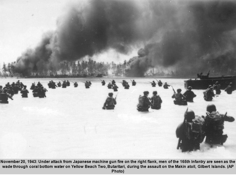 42 November 20, 1943: Under attack from Japanese machine gun fire on the right flank, men of the 165th Infantry are seen as the wade through coral bottom water on Yellow Beach Two, Butaritari, during the assault on the Makin atoll, Gilbert Islands.