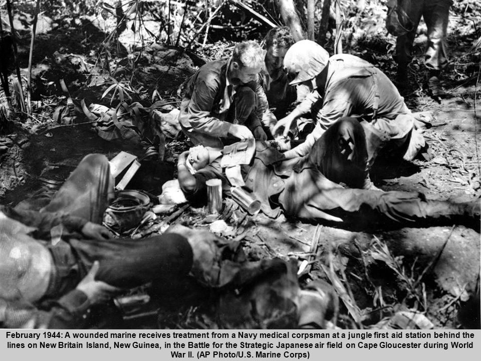 51 February 1944: A wounded marine receives treatment from a Navy medical corpsman at a jungle first aid station behind the lines on New Britain Islan