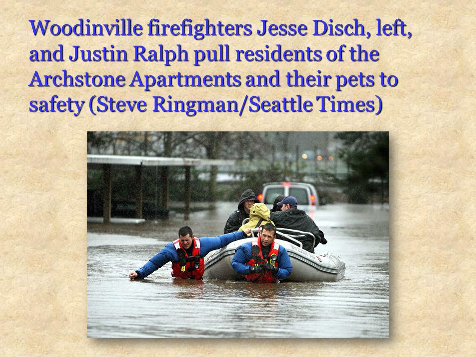 Woodinville firefighters Jesse Disch, left, and Justin Ralph pull residents of the Archstone Apartments and their pets to safety (Steve Ringman/Seattle Times)