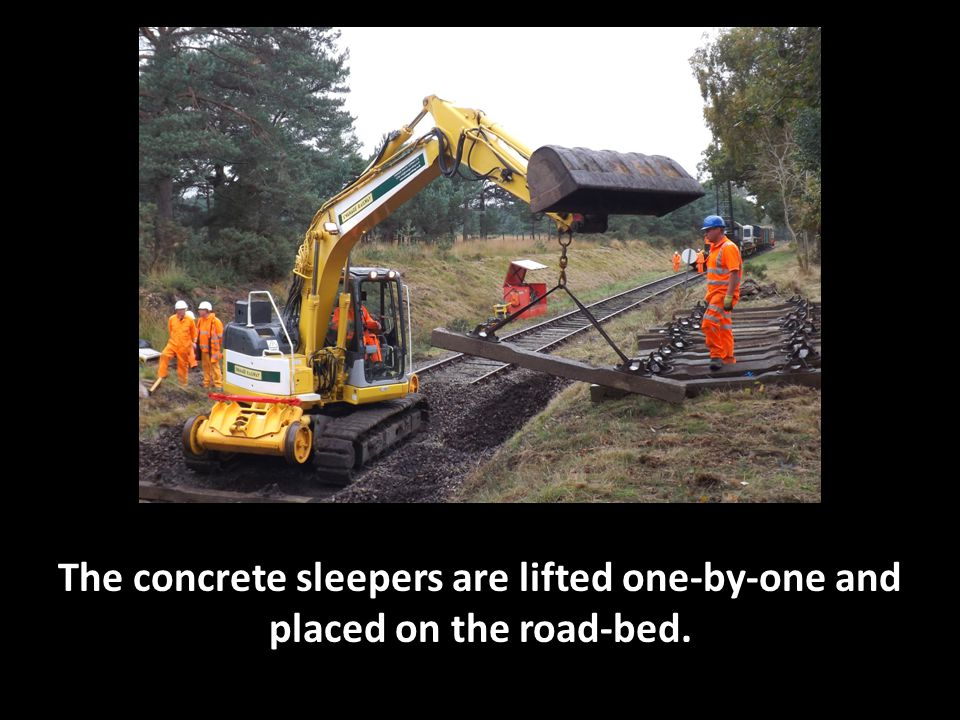 The concrete sleepers are lifted one-by-one and placed on the road-bed.