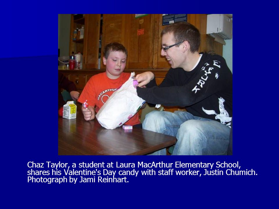 Chaz Taylor, a student at Laura MacArthur Elementary School, shares his Valentine s Day candy with staff worker, Justin Chumich.