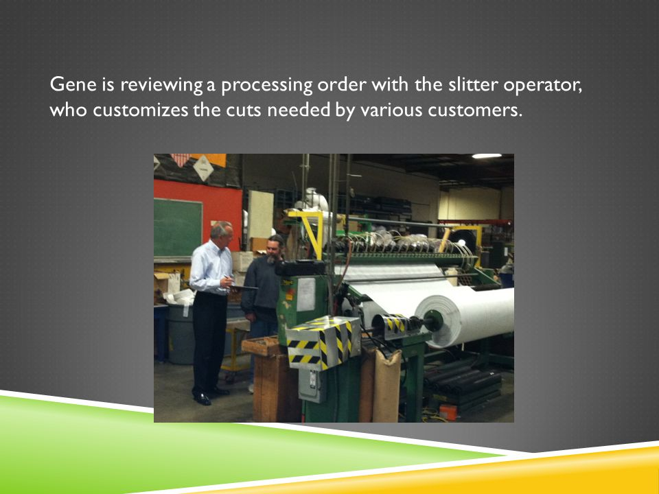 Gene is reviewing a processing order with the slitter operator, who customizes the cuts needed by various customers.
