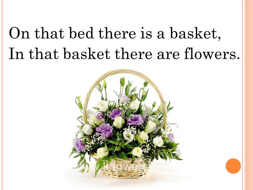 On that bed there is a basket, In that basket there are flowers.
