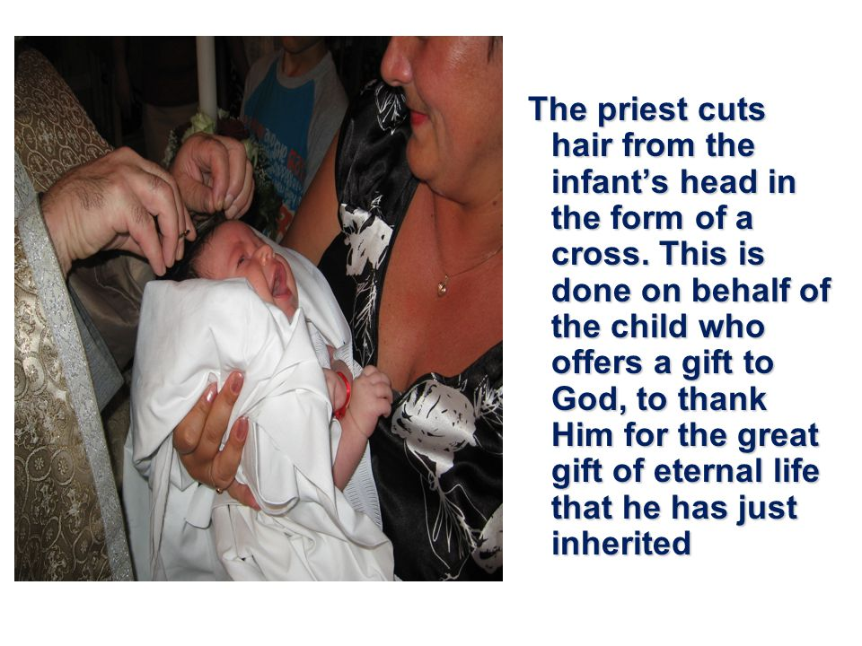 The priest cuts hair from the infant's head in the form of a cross.