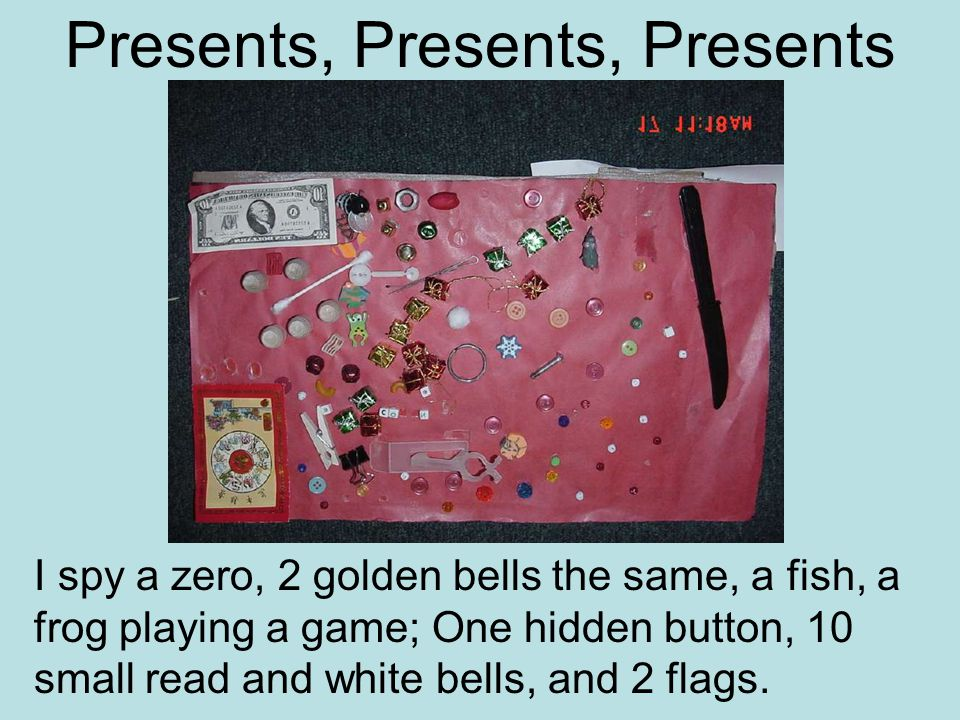 Presents, Presents, Presents I spy a zero, 2 golden bells the same, a fish, a frog playing a game; One hidden button, 10 small read and white bells, and 2 flags.