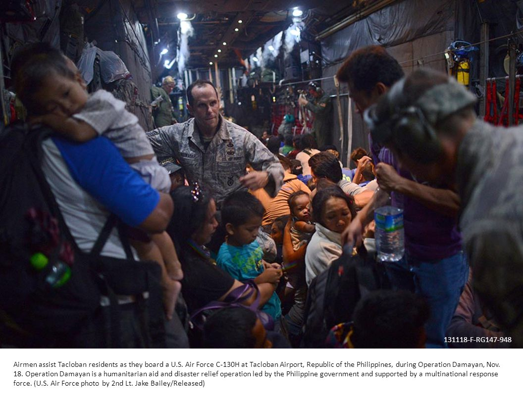 Airmen assist Tacloban residents as they board a U.S.