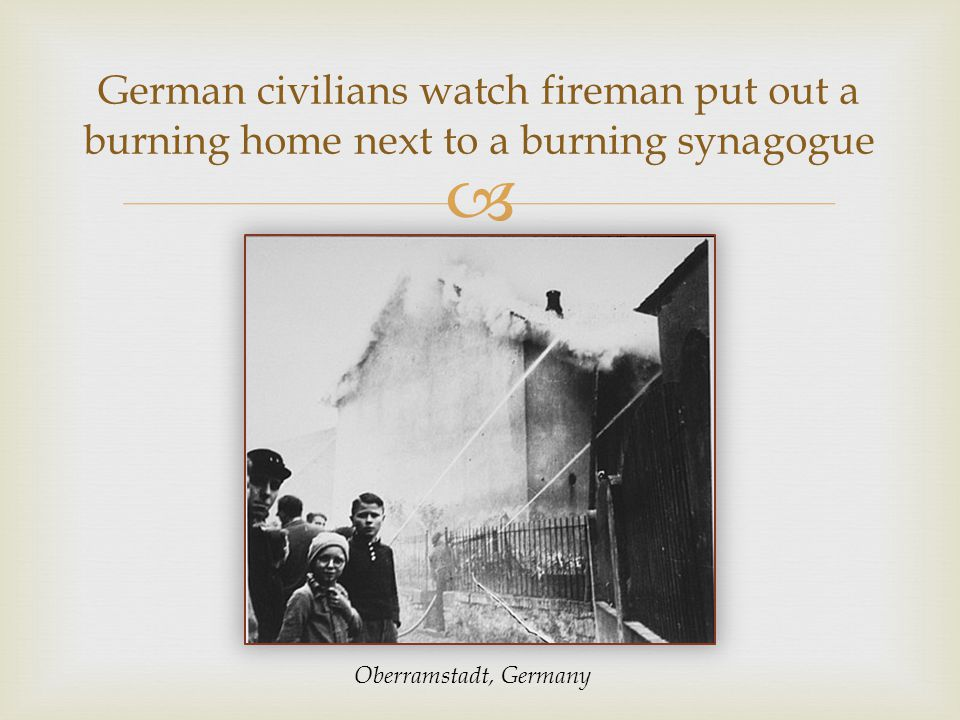  German civilians watch fireman put out a burning home next to a burning synagogue Oberramstadt, Germany