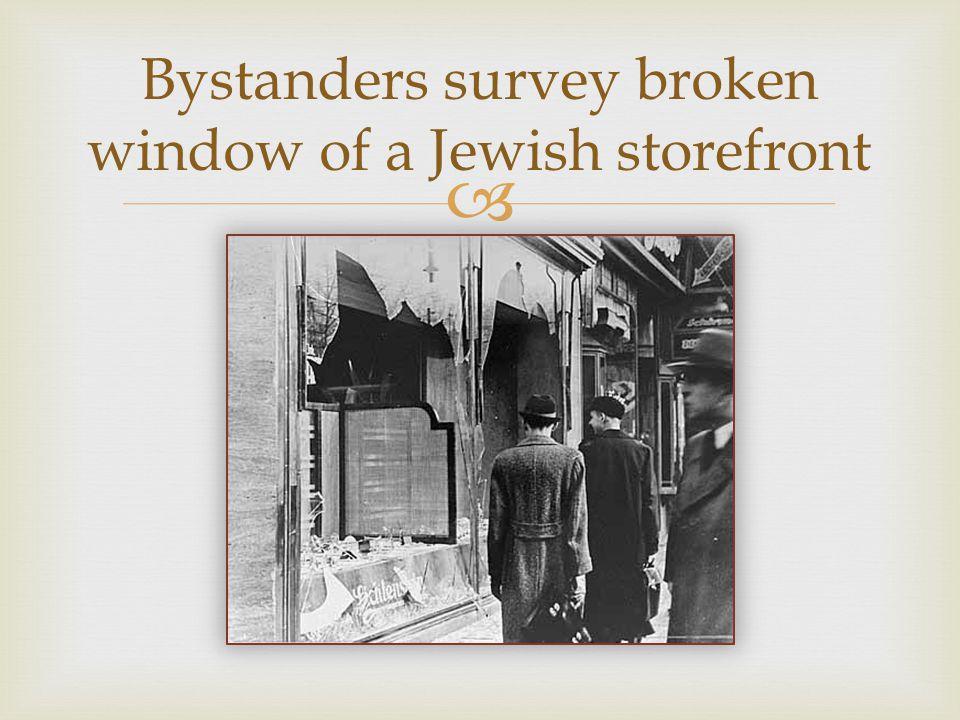  Bystanders survey broken window of a Jewish storefront